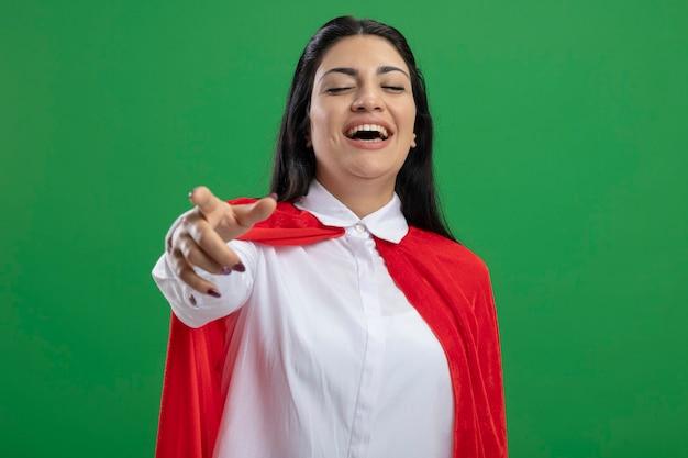 Смеющаяся молодая кавказская девушка-супергерой показывает пальцем и смотрит в камеру с закрытыми глазами, изолированными на зеленом фоне