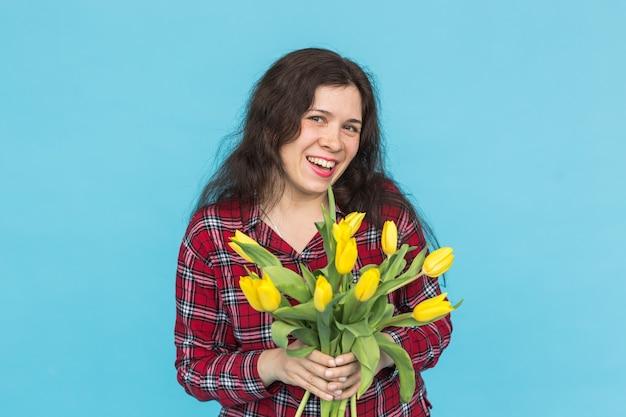 Смеющаяся молодая кавказская женщина с букетом тюльпанов на синей стене