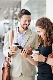 Смеющиеся молодые коллеги пьют кофе на вынос и смотрят забавные видеоролики на смартфоне во время перерыва