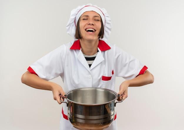 Ridendo giovane cuoco femminile in uniforme del cuoco unico che solleva pentola con gli occhi chiusi isolati su sfondo bianco