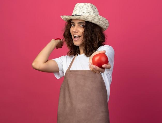 Ridendo giovane giardiniere femminile in uniforme che indossa cappello da giardinaggio tenendo il pomodoro isolato sul rosa