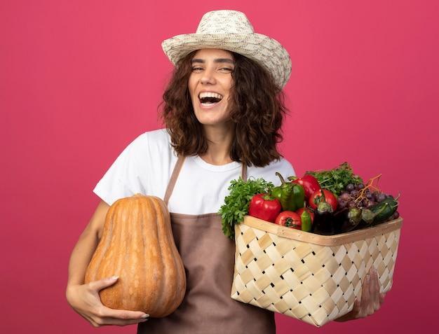Ridendo giovane giardiniere femminile in uniforme che indossa cappello da giardinaggio tenendo il cesto di verdure con zucca isolato sul rosa