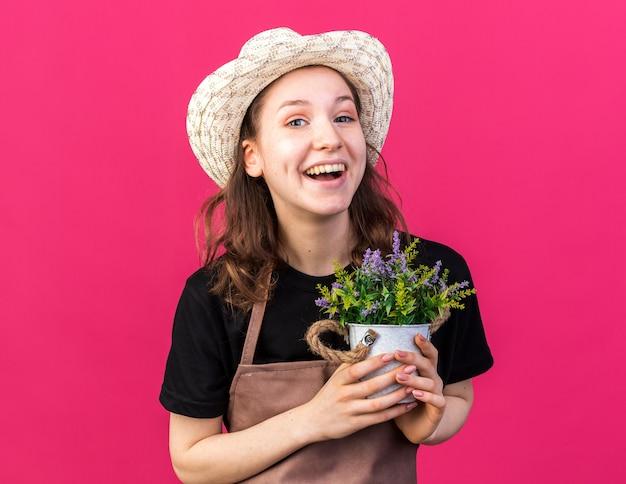 植木鉢に花を保持しているガーデニング帽子をかぶって笑う若い女性の庭師
