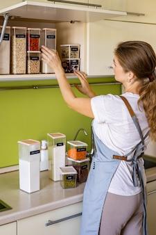食器棚のキッチンで片付けの一般的な掃除中にポーズをとって笑う若い女性主婦