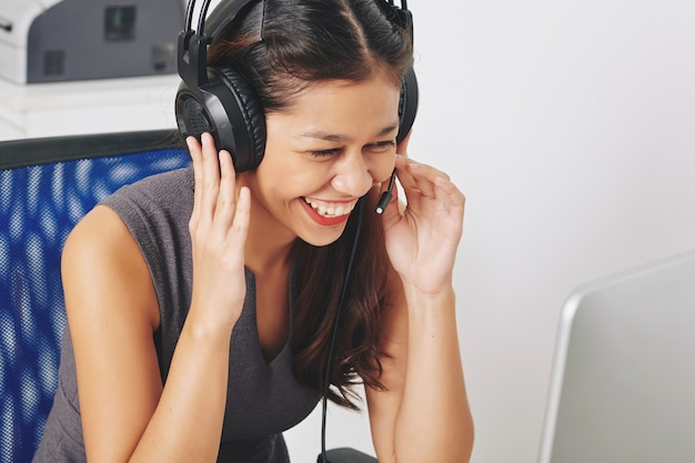 Laughing young female technical support operator answering questions of client