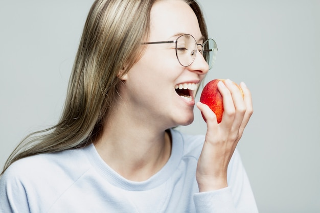Laughing young girl eating an apple. close-up. healthy nutrition and vitamins.
