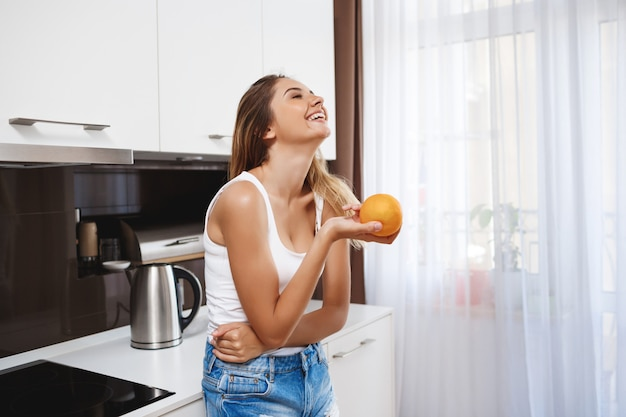 Laughing young girl holding orange at kitchen