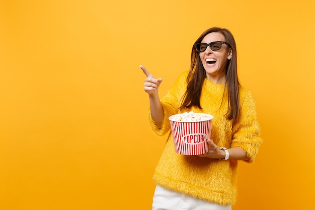 3d 아이맥스 안경을 쓴 어린 소녀가 검지 손가락을 가리키고, 영화를 보고, 밝은 노란색 배경에 격리된 팝콘 양동이를 들고 웃고 있습니다. 영화, 라이프 스타일 개념에서 사람들은 진실한 감정.