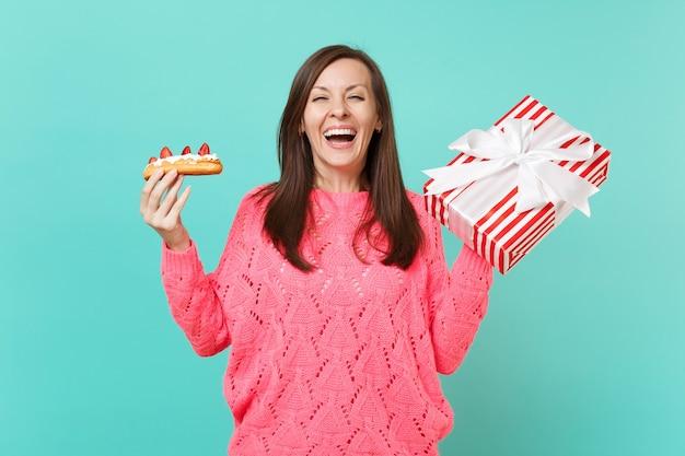 ニットピンクのセーターで笑っている若い女の子は、青い背景で隔離のギフトリボンとエクレアケーキ赤い縞模様のプレゼントボックスを保持します。バレンタインの女性の日の誕生日の休日のコンセプト。コピースペースをモックアップします。