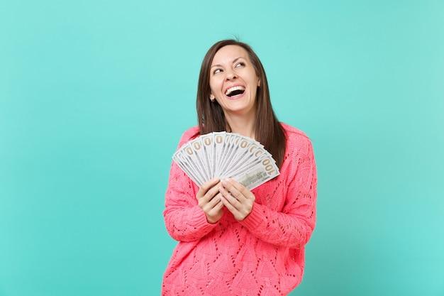 スタジオの青い壁の背景に分離されたドル紙幣の現金のお金の束を手に持って見上げるニットピンクのセーターで笑っている若い女の子。人々のライフスタイルの概念。コピースペースをモックアップします。