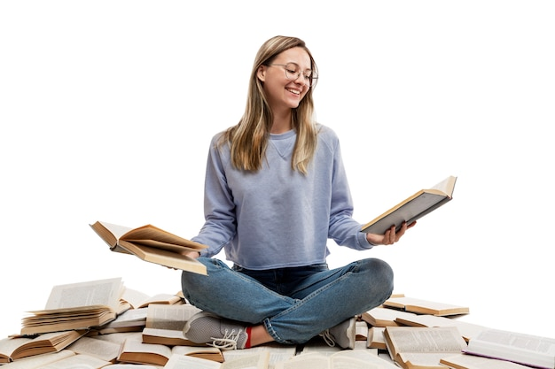 A laughing young girl in jeans and a blue t-shirt sits on a pile of opened books and holds books in her hands. education and knowledge. .