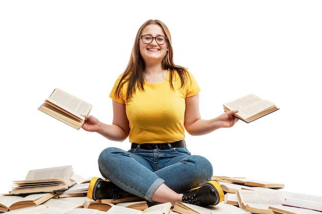 A laughing young girl in jeans and a blue t-shirt sits on a pile of opened books and holds books in her hands