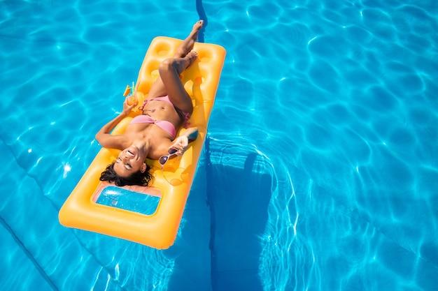 Смеющаяся молодая девушка, лежа на надувном матрасе в бассейне