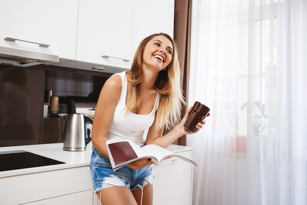 Laughing young girl reading magazine and drinking coffee