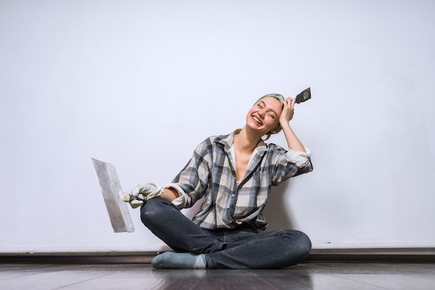 A laughing young girl in a shirt is sitting on the floor, doing repairs in her apartment, holding a spatula in her hands