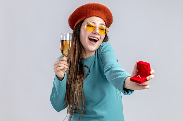 Ridendo ragazza il giorno di san valentino indossando un cappello con gli occhiali tenendo un bicchiere di champagne con anello di nozze isolato su sfondo bianco