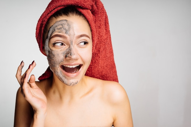 A laughing young girl with a red towel on her head applies a useful clay mask on her face, a day spa