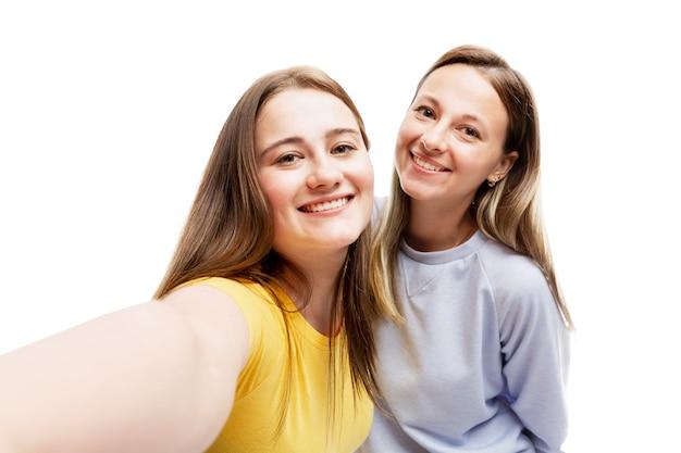 笑う若いガールフレンドは自分撮りをします。愛、優しさ、友情。白い壁に隔離。