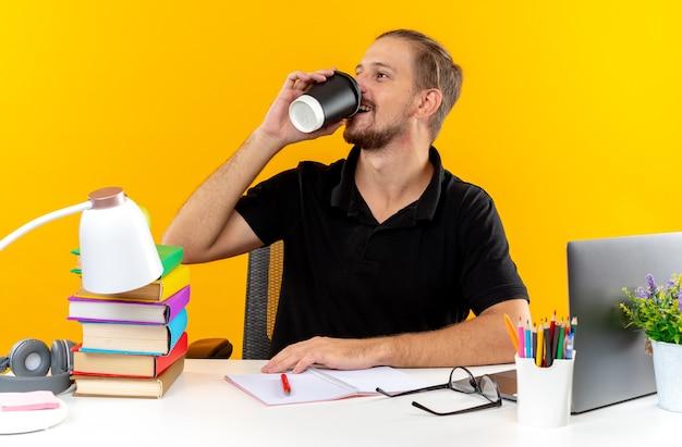 Смеющийся молодой парень студент сидит за столом со школьными инструментами пьет кофе