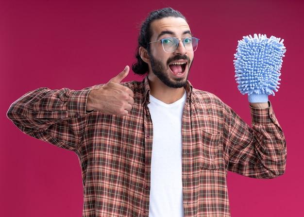 Смеющийся молодой красивый уборщик в футболке, держащий тряпку для уборки, показывая большой палец вверх, изолированный на розовой стене