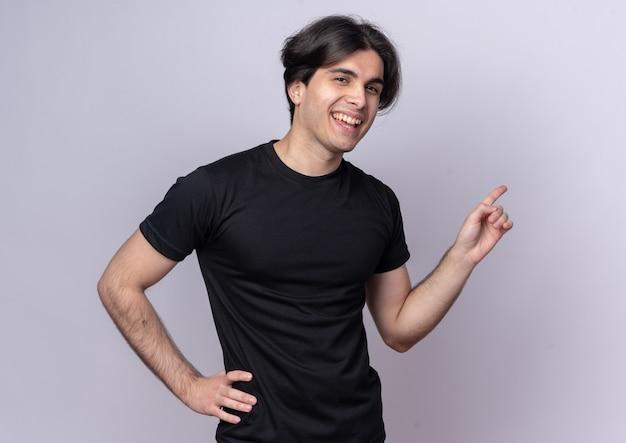 Ridere giovane bel ragazzo che indossa t-shirt nera indica dietro mettendo la mano sull'anca isolata sul muro bianco con copia spazio