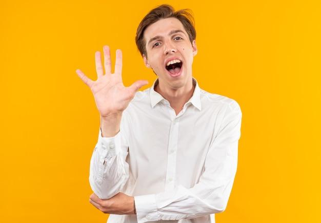 Ridendo giovane bel ragazzo che indossa una camicia bianca che mostra cinque isolati sul muro arancione