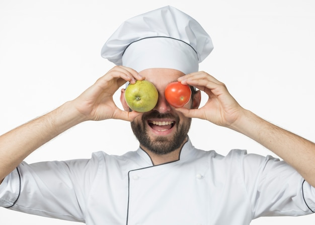 Laughing young male chef holding apple and red tomato in front of his eyes