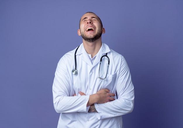 Смеющийся молодой врач-мужчина в медицинском халате и стетоскопе, скрестив руки на животе с закрытыми глазами, изолирован на фиолетовом фоне с копией пространства