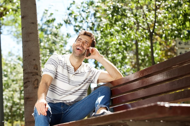 Laughing young man sitting outdoors on bench and using mobile phone