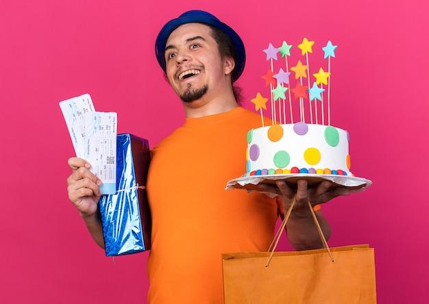 ギフトボックスとチケットとケーキを保持しているパーティーハットを身に着けている若い男を笑う