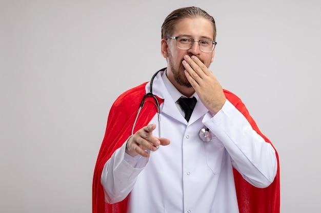 청진 기 및 안경 의료 가운을 입고 젊은 슈퍼 히어로 남자 웃 고 흰색 배경에 고립 된 제스처를 보여주는 손으로 입을 덮여