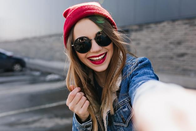 Giovane donna di risata in cappello rosso casuale che fa selfie. ritratto all'aperto di una magnifica ragazza in posa sul muro urbano con un sorriso sincero.