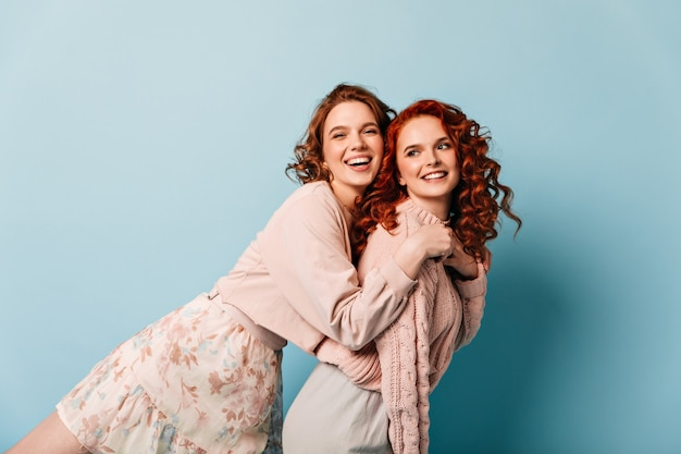 Ridendo giovane donna che abbraccia il migliore amico. belle ragazze che hanno divertimento su sfondo blu.
