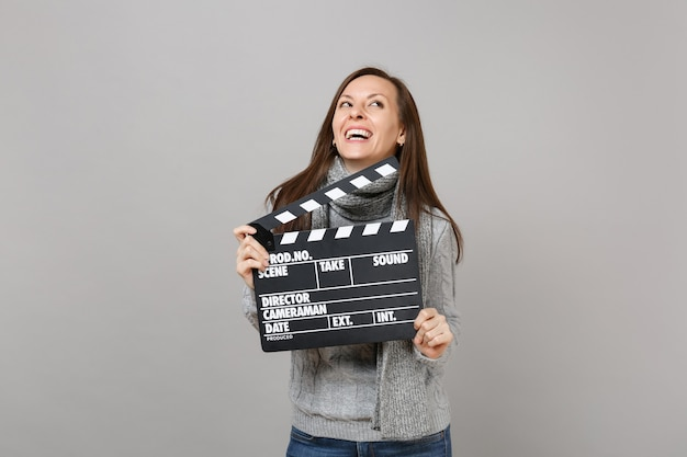 Laughing young woman in gray sweater, scarf looking up hold classic black film making clapperboard isolated on grey background. healthy fashion lifestyle, people sincere emotions, cold season concept.