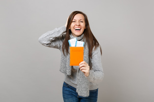 Laughing young woman in gray sweater, scarf put hand on head, holding passport boarding pass ticket isolated on grey background. healthy fashion lifestyle people sincere emotions, cold season concept.