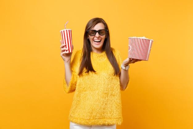 3d 아이맥스 안경을 쓴 젊은 여성이 영화를 보고 웃고, 노란색 배경에 격리된 팝콘 양동이, 플라스틱 컵 콜라 또는 소다를 들고 있습니다. 영화, 라이프 스타일 개념에서 사람들은 진실한 감정.