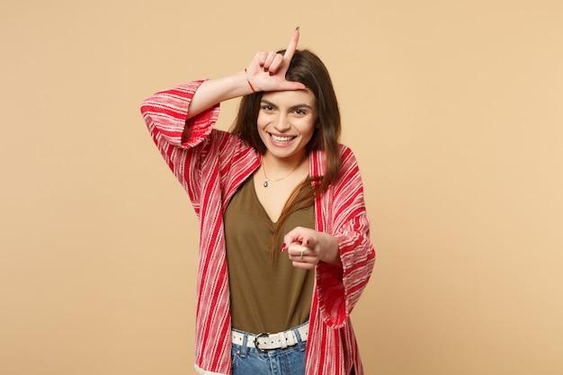 Смеющаяся молодая женщина в повседневной одежде, показывающая жест проигравшего, указывая указательным пальцем на камеру, изолированную на пастельных бежевых стенах. люди искренние эмоции, концепция образа жизни. копируйте пространство для копирования.