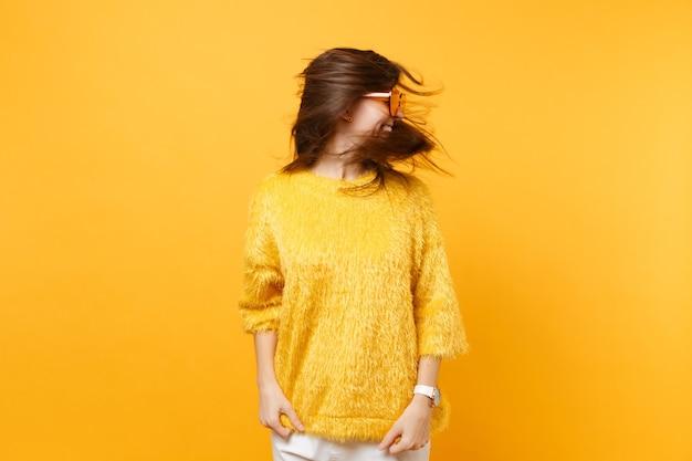 Смеющаяся молодая женщина в меховом свитере, сердце оранжевые очки дурачиться в студии с волнистыми волосами, изолированными на ярко-желтом фоне. люди искренние эмоции, концепция образа жизни. рекламная площадка.