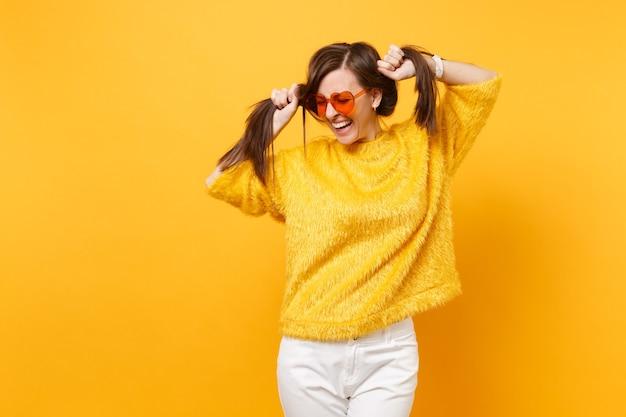 Смеющаяся молодая женщина в меховом свитере, белых штанах, очках сердца оранжевого цвета, держа волосы, как хвостики, изолированные на ярко-желтом фоне. люди искренние эмоции, концепция образа жизни. рекламная площадка.