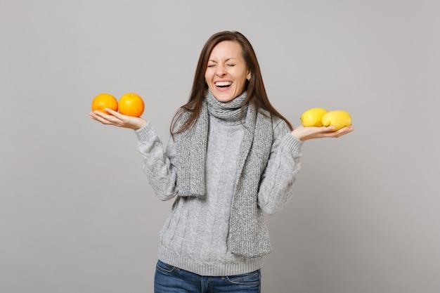 Смеющаяся молодая женщина в сером свитере, шарфе с закрытыми глазами держит апельсины лимоны, изолированные на сером фоне. концепция холодного сезона людей здорового образа жизни моды искренние эмоции. копируйте пространство для копирования.