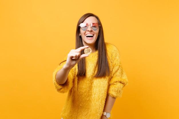 밝은 노란색 배경에 격리된 금색 미래 통화의 금속 동전인 비트코인을 들고 심장 안경을 쓴 젊은 여성을 웃고 있습니다. 사람들은 진심 어린 감정, 라이프 스타일 개념입니다. 광고 영역입니다.