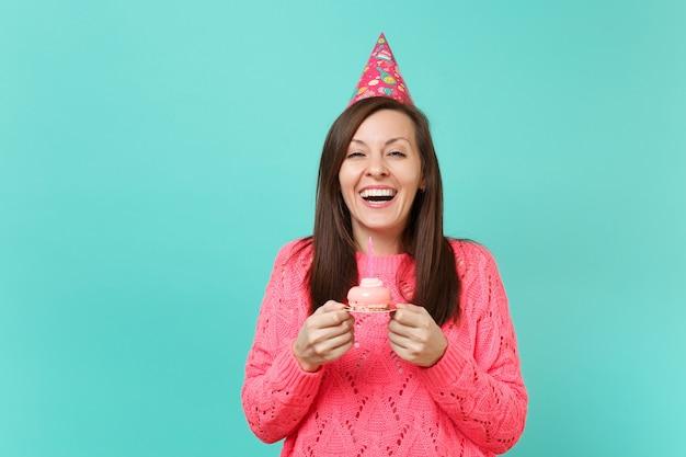 파란색 청록색 벽 배경 스튜디오 초상화에 격리된 촛불을 들고 손으로 케이크를 들고 있는 분홍색 스웨터와 생일 모자를 쓴 젊은 여성을 웃고 있습니다. 사람들이 라이프 스타일 개념입니다. 복사 공간을 비웃습니다.