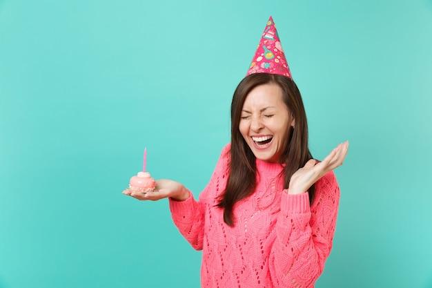 분홍색 스웨터를 입은 웃고 있는 젊은 여성, 생일 모자는 촛불을 들고 손으로 케이크를 들고 파란색 배경에 고립된 채 눈을 감고 손을 펼치고 있습니다. 사람들이 라이프 스타일 개념입니다. 복사 공간을 비웃습니다.