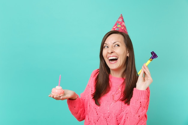 핑크색 스웨터를 입은 젊은 여성, 파란색 벽 배경에 격리된 촛불이 든 손 케이크를 들고 있는 파이프를 들고 있는 생일 모자를 웃고 있습니다. 사람들이 라이프 스타일 개념입니다. 복사 공간을 비웃습니다.