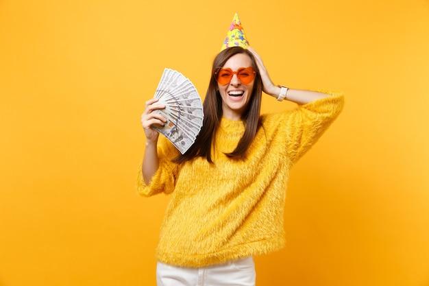 Смеющаяся молодая женщина в оранжевой шляпе на день рождения в очках с сердечками, положив руку на голову, держа пачку долларов наличными деньгами, празднуя изолированные на желтом фоне. люди искренние эмоции, образ жизни.