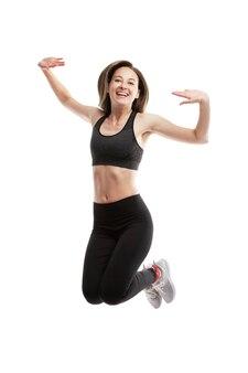 Смеющаяся молодая женщина в спортивной одежде прыгает