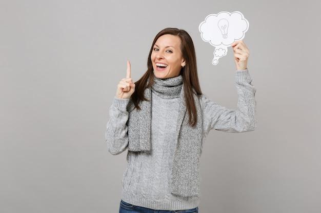 스웨터를 입은 젊은 여성을 웃고, 멋진 새로운 아이디어로 검지 손가락을 들고 있는 스카프, 회색 배경에 전구가 분리된 구름을 말합니다. 건강한 패션 라이프스타일 사람들은 추운 계절 개념을 감정합니다.
