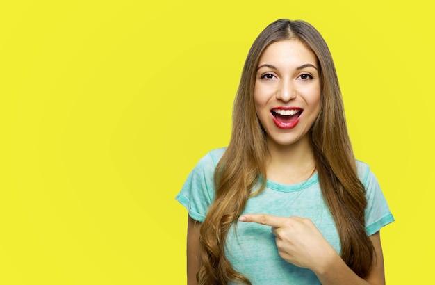 Смеющаяся молодая женщина в футболке указывая пальцем