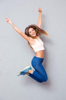 Смеющаяся молодая женщина прыгает
