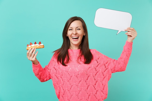 Laughing young woman in knitted pink sweater holding eclair cake, empty blank say cloud speech bubble for promotional content isolated on blue background. people lifestyle concept. mock up copy space.